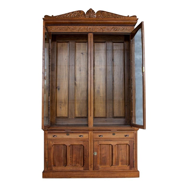 This solid ash two-piece bookcase is a great example of traditional Victorian-era furniture. Two drawers, as well as two lower cabinets, provide concealed storage The upper case, with its original wavy glass, allows for the display of special