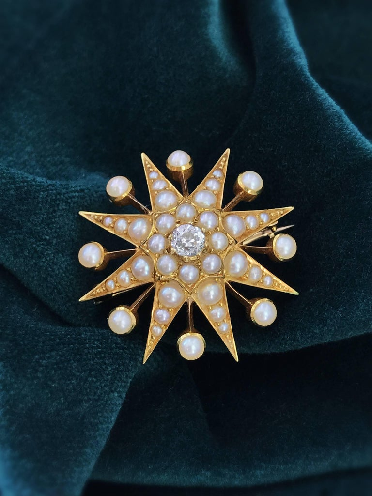 A late Victorian 15ct gold diamond and split pearl star brooch. The old-cut diamond and split pearl cluster, with graduated split pearl ray surround. May be worn as a pendant. Estimated diamond weight 0.25ct, H-I colour, SI clarity. Diameter 3.1cms.
