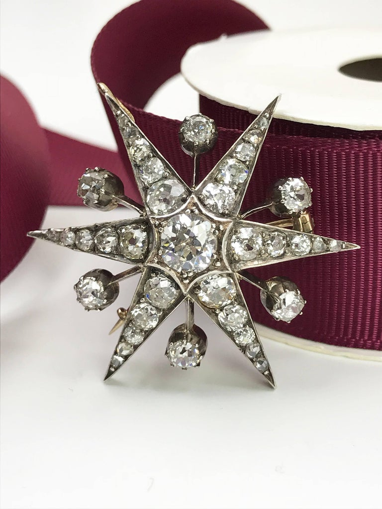 A late Victorian diamond star brooch. One of the favorite brooch style from Queen Elizabeth II. Set with 9ct gold front and silver back, old-cut diamond with vari-cut diamond rays and spacers. May be worn as a pendant. Estimated total diamond weight