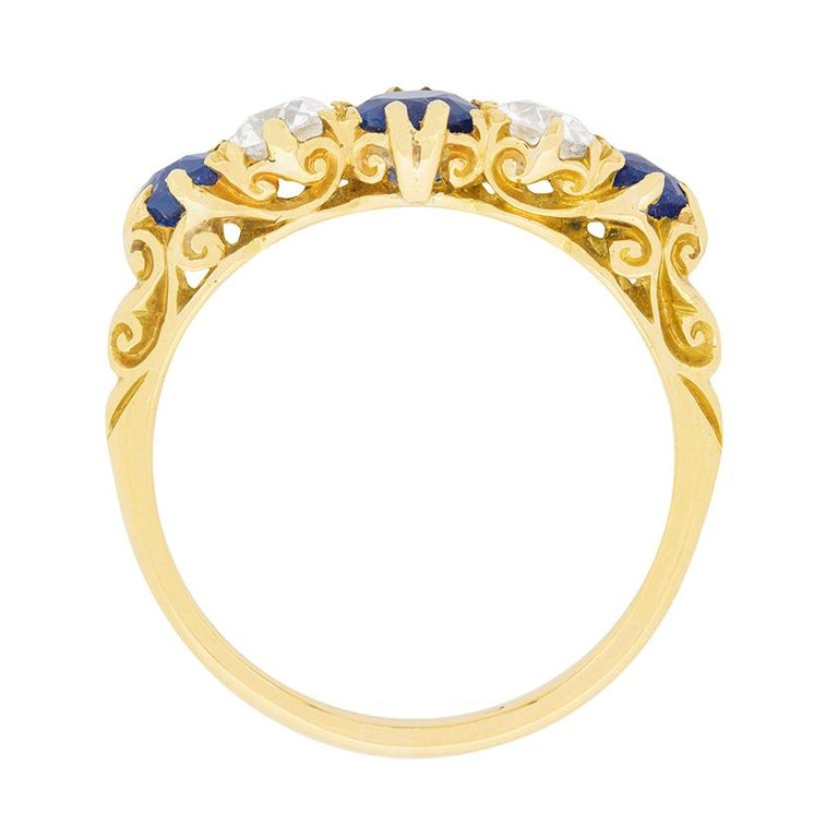 This late Victorian era five stone sapphire and diamond ring is a quintessential example of one of the era's most loved styles.  This original period ring features three gorgeous, old cut natural sapphires alternating with two 0.25ct old cut