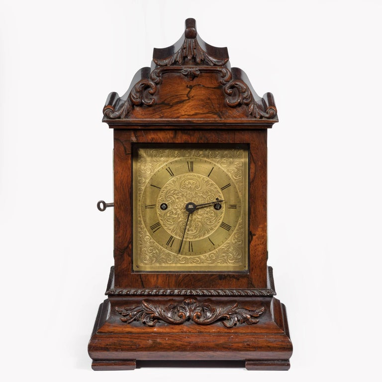 The case carved in high relief with scrolls and an acanthus leaf finial, the gilt face finely chased with further scrolls and signed on the dial, with a discreet/silent lever above the XII, striking two-train fusee movement, stirrup pendulum with
