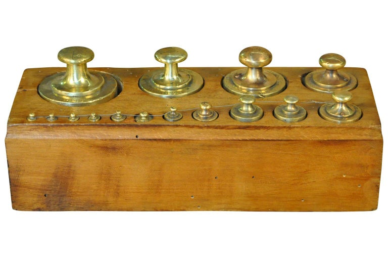 A later 19th century set of weights in brass housed in their wooden box. Weights such as these were used with different scales - balances - whether for apothecary, jewelers, confectionery, grocers. A charming accent piece for a kitchen island,