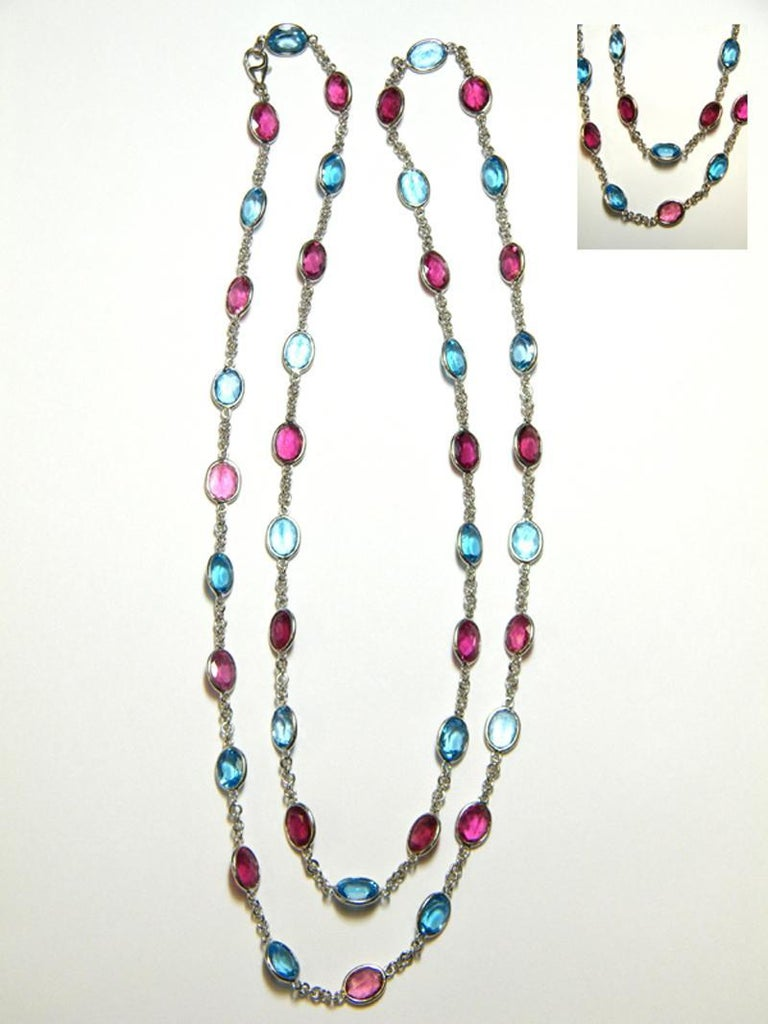 18 karat white gold 31.25 inch chain with oval Pink Tourmaline and Blue Topaz (42) oval  8 x 6 mm stones, 21 Pink Tourmaline approximately 23.52 carats total weight  and 21 Blue Topaz approximately 29.61 carats total weight. Lobster style clasp.