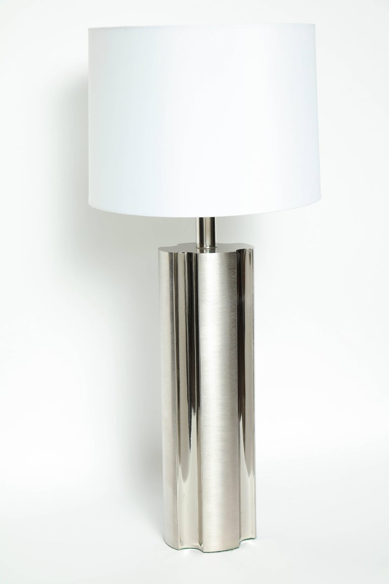 Pair of modernist fluted brushed steel column lamps with contrasting polished steel indentations. Lamps have been rewired for use in the USA with clear cords and nickel sockets. Shades not included.