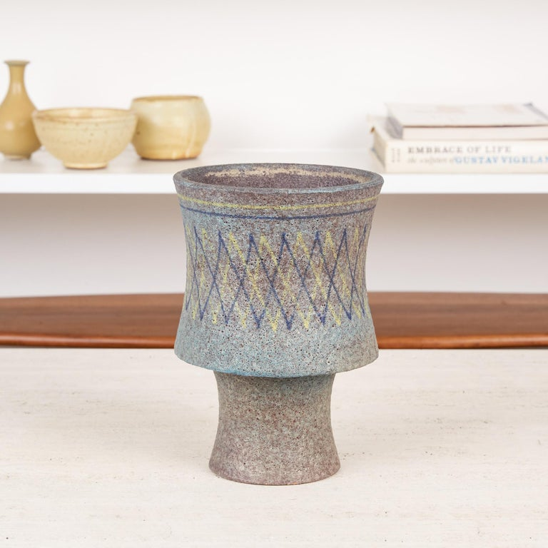 Ceramic chalice vase by Aldo Londi for Bitossi, Italy, circa 1960s. The vase features a wide curvaceous upper section that sits atop a thinner convex stem. It is covered in a muted turquoise lava glaze with underlying lavender accents. The upper
