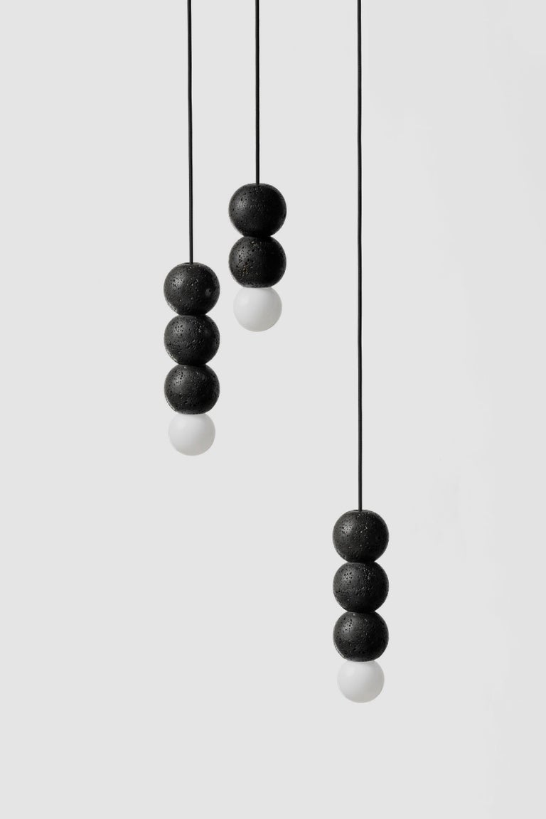 """Material: Lava Stone Fittings: Black Aluminum Color: Black Dimension: 90 x 90 x 320 mm Weight: 1.4 kg Cord: 3000 mm Light Source: E27 G80 CCT: 3200 K CRI: 85 Ra Flux: 600 lm Supply: 220 V Wattage: 7 W  About the Artist/ Designer: The word """"buzao"""""""