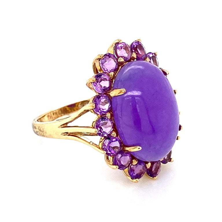 "Beautiful and Striking! Elegant and finely detailed Lavender Jade and Amethyst Cocktail Ring. Center set with a securely nestled oval Lavender Jade, surrounded by Amethyst. Measuring approx. 0.74"" w x 0.01"" h x 1.08"" d Hand crafted in 10 Karat"