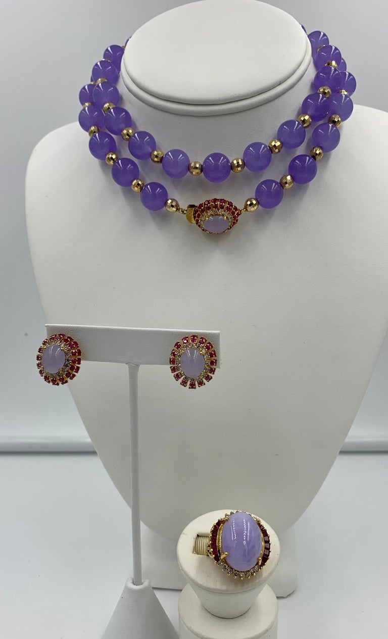 A spectacular Lavender Jade, Ruby, Diamond Suite.   The suite comprising a necklace, earrings and ring each with gorgeous Lavender Jade oval cabochons with a 17 Carat Jade Cabochon in the ring.  The Jade cabochons are surrounded by 1.25 Carats of