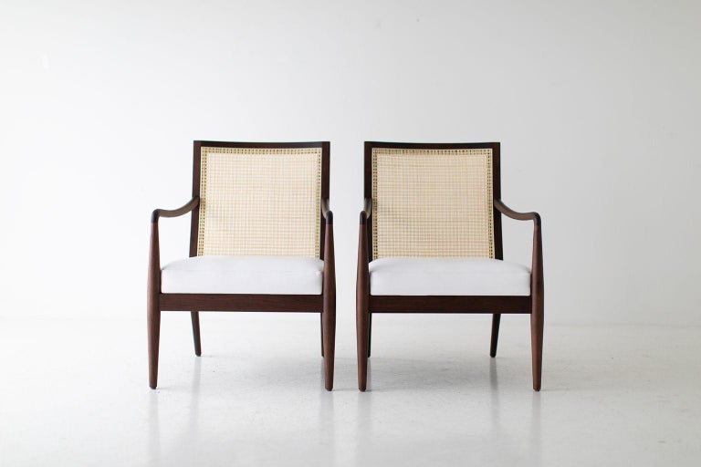 Designer: Lawrence Peabody  Manufacturer: Craft Associates Furniture Period/Model: Mid-Century Modern Specs: Walnut, cane, leather  These Lawrence Peabody modern cane back arm chairs for Craft Associates Furniture are expertly handcrafted and
