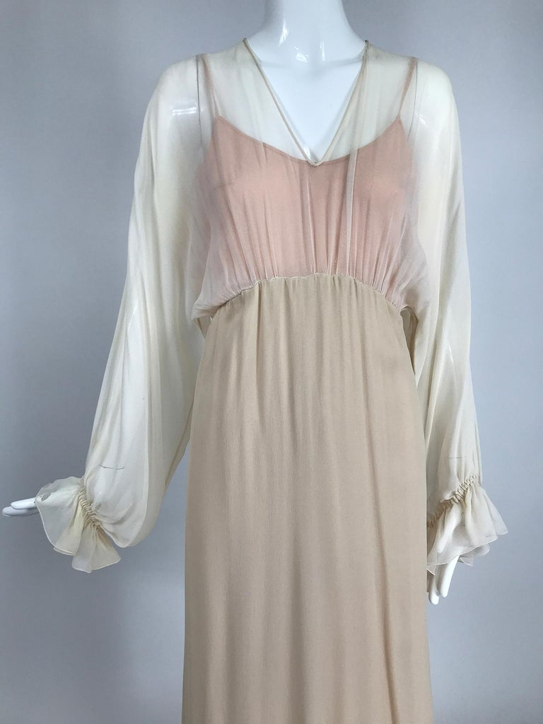 Tonal layered silk chiffon, bat wing, poet sleeve, maxi dress from the 1970s. This beautiful dress is done in tone on tone peachy/nude chiffon. The dress bodice has a V neckline and draped bat wing sleeves that are gathered into cased elastic