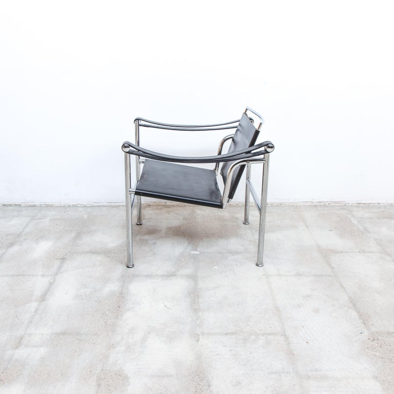 A nicely patinated LC1 sling chair, black leather on chrome frames. The leather elements connected with steel tension springs.
