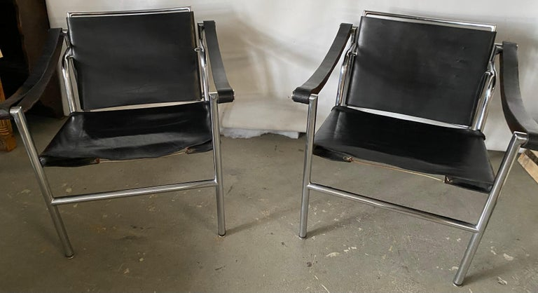 The LC1 style occasional lounging arm chairs with leather and springs straps and chrome frame are in very good condition. These are not marked but could possibly be LC1 chairs since there was a period when these chairs were manufactured but not