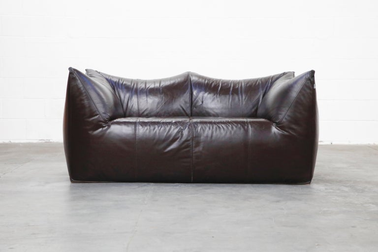 This incredible 'Le Bambole' loveseat by Mario Bellini for B&B Italia has thick gorgeous dark brown hide leather. The color is a dark deep brown that it looks black in lower light settings and beautiful dark brown in brighter settings. Designed in