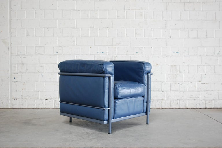 This LC2 armchair in blue leather was designed by Le Corbusier/ Pierre Jeanneret/ Charlotte Perriand and produced by Cassina.  It features a blue/ grey colored tubular steel frame. Some marks on the tubular frame.