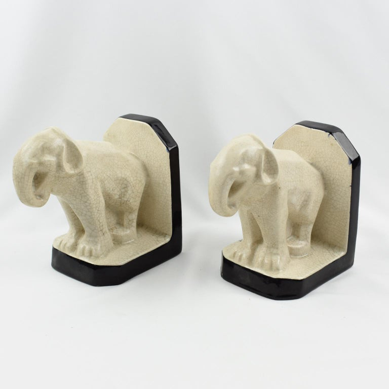 Superb Art Deco pair of crackle ceramic bookends by Le Moine, France. Off-white colored crackle glaze ceramic or faience sculpture featuring a pair of elephants with contrasted black enameled glaze application. Marked 'Lemoine' on base of each