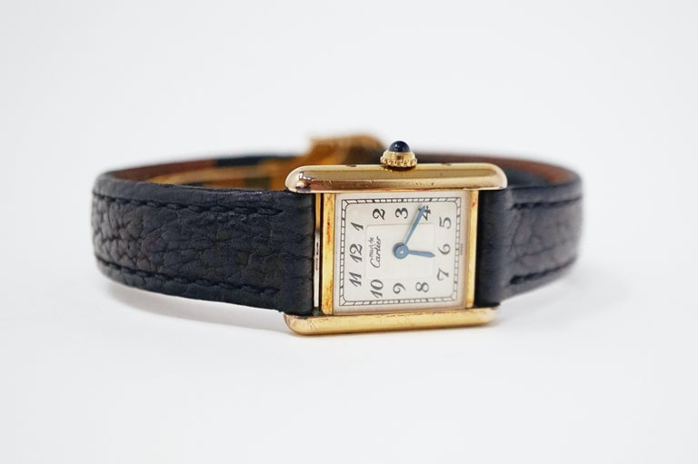 Le Must de Cartier Gold Vermeil 925 Tank Watch - 20mm Argent case - Arabic numeral markers - Black leather band with hidden deployment clasp - Quartz movement - Sapphire glass  Designed in 1917 by Louis Cartier, the Tank is an iconic watch adored by