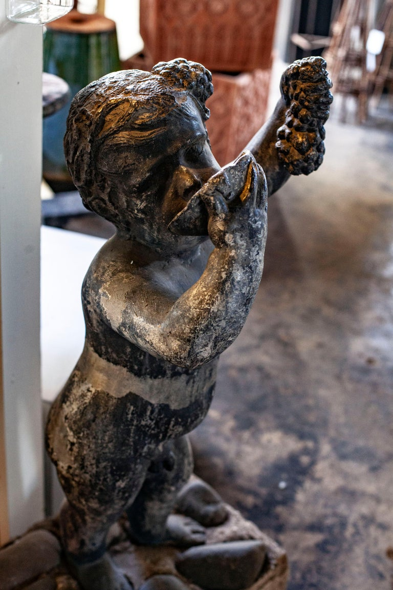 This lead sculpture bears the face of one of the most recognizable faces in traditional art. The cherub, or putto has been represented in a wide variety of themes ranging from mythology to renaissance art. Enjoying a bountiful harvest, this cherub