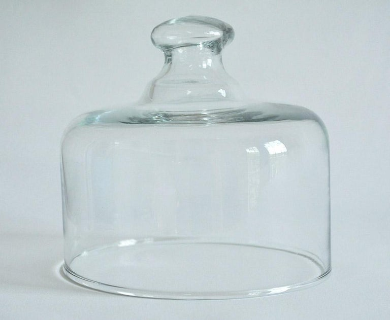 French patisserie glass cloche with an open glass knob handle. Smooth and polished glass, these were used in French patisseries. Bistros or home to cover and display pastries and cheese. Simple yet elegant, a wonderful addition to any table, kitchen