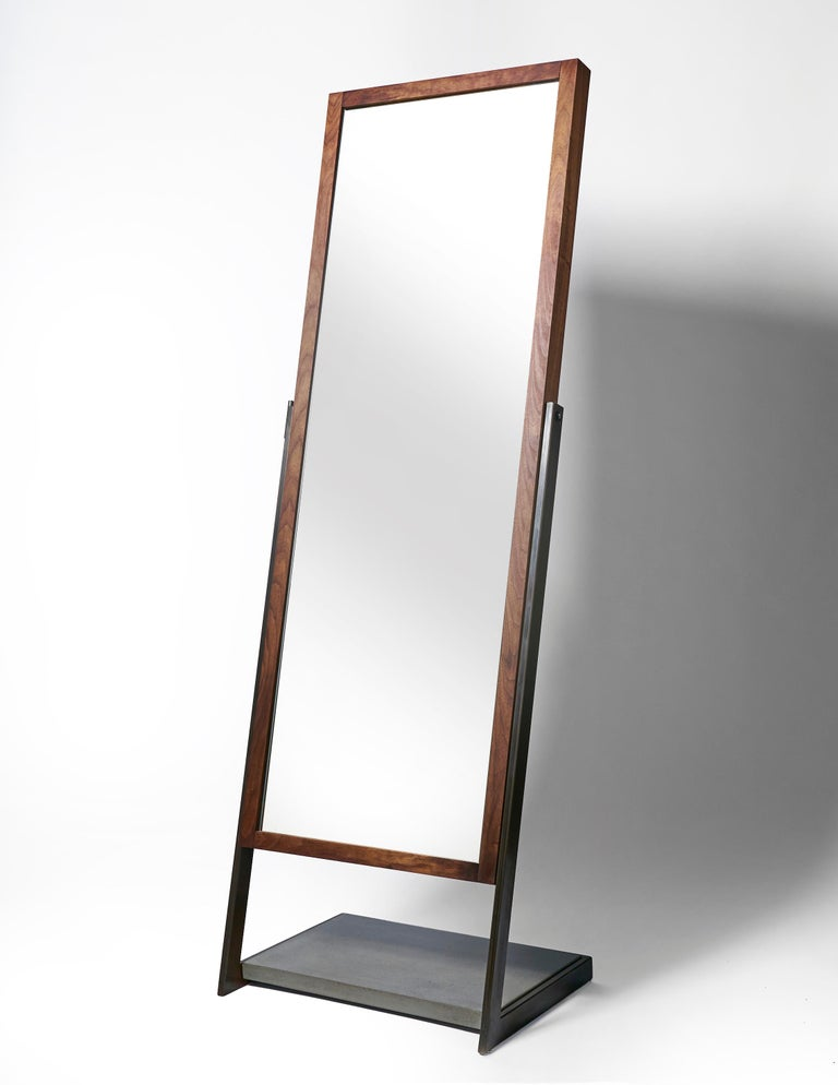 Full length mirror imagined in a new way with a perfect balance in both materials and lines. A wrap around hand blackened steel frame holds a lower platform section of charcoal concrete at the base. Suspended in this frame is a full length mirror