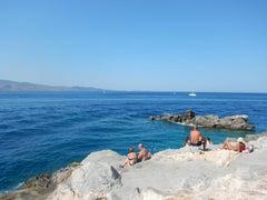 Sunbathers on the rocks at Spilia, Hydra, Greece