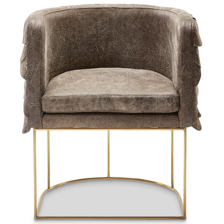 Inspired by the South African birds of prey, this contemporary and handmade tub chair, by Egg Designs, is clad in a series of distressed leather circles, each one hand pinned to create an overlapping pattern reminiscent of a bird's wing.