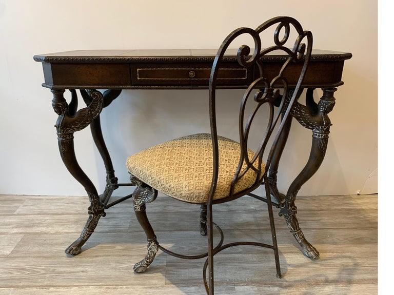 Continental leather and bronze finished metal console writing table with matching chair. The leather covered surface with center drawer resting on four legs with winged caryatid figures. In the manner of Maitland Smith. The chair is 16 inches wide,