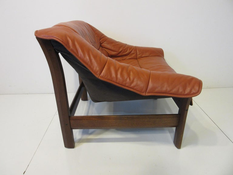 A leather covered lounge chair with a Jacaranda rosewood frame designed by Percival Lafer with comfort and style in mind. Made in Brazil the designers and crafts people who made these midcentury and modern pieces are finally getting the recognition