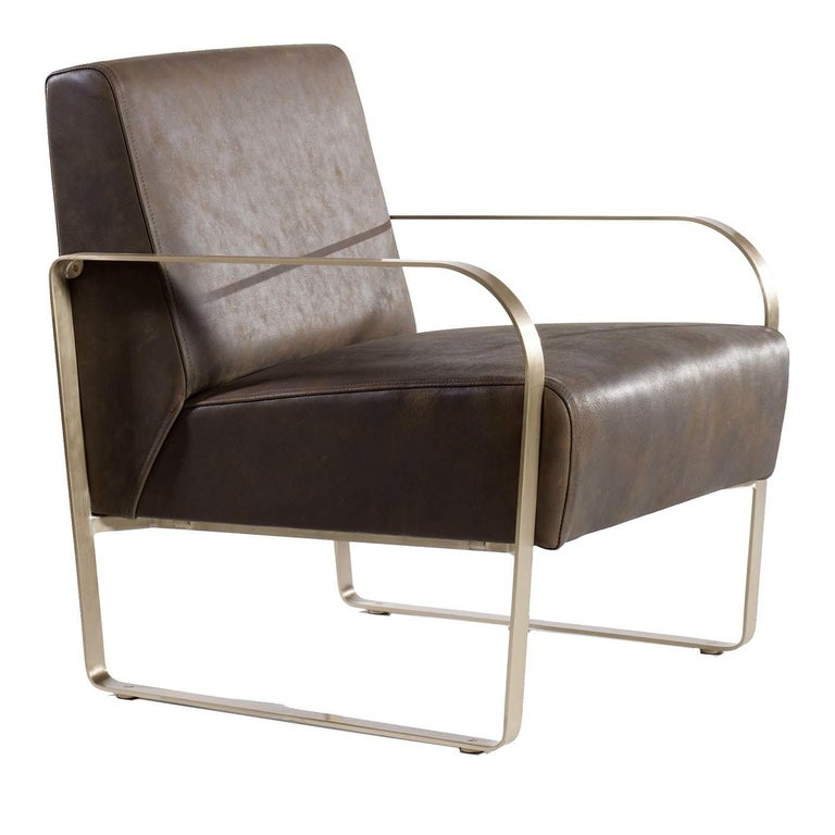 A combination of solid brass and soft leather merges in the elegant proportions of this armchair. The cushioned, tailored seat and backrest have a crisp and geometric Silhouette, covered in soft hand-stitched leather with a roomy set-back design for
