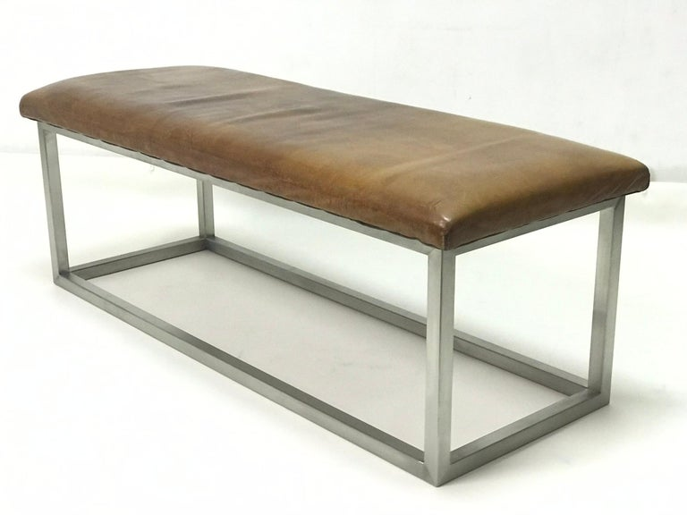 The bench has strong leather completed the stainless steel construction. The leather is in the original patina.