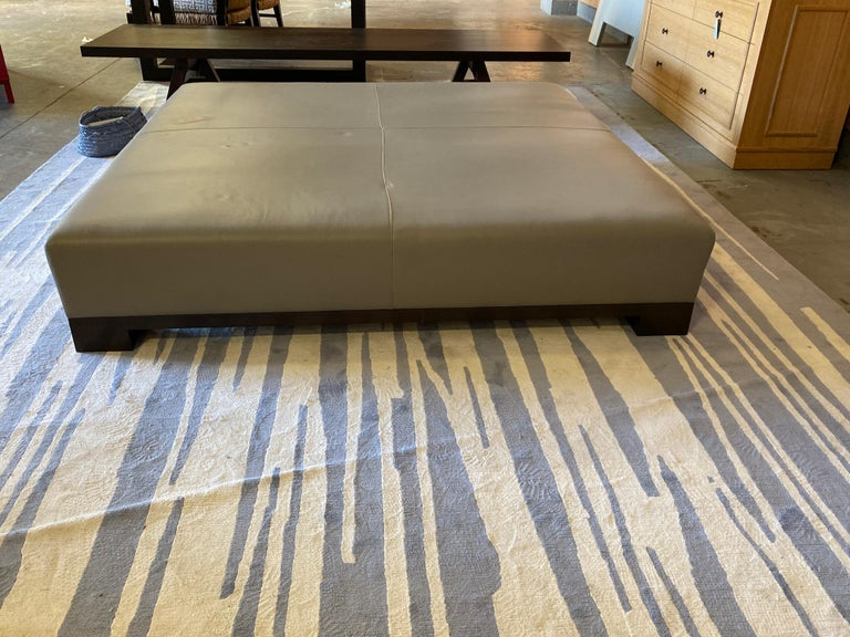 Custom upholstered leather coffee table in extra large size in gray smooth leather. This piece was custom made for a very large living room in a Hamptons home. Wood base with dark stained wood legs. Some scuffs on leg edges. Leather sags in some