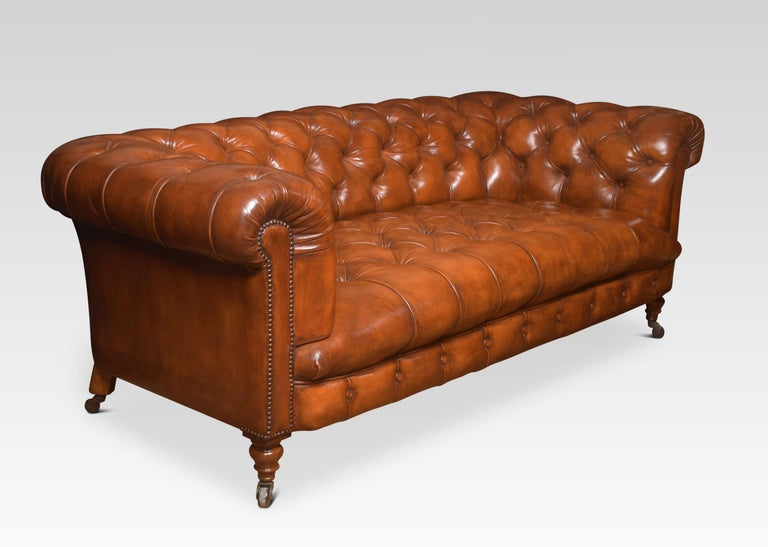 Large brown leather Chesterfield sofa, having deep buttoned back and seat, raised up on turned feet with brass ceramic castors. Good solid condition, the leather has been replaced and hand-dyed.