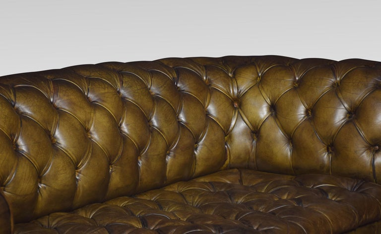 Large three-seat green leather Chesterfield sofa, having deep buttoned back and seat, raised up on turned feet with brass ceramic castors. Good solid condition, the leather is soft, nicely worn in. Dimensions: Height 32 inches height to seat 19.5