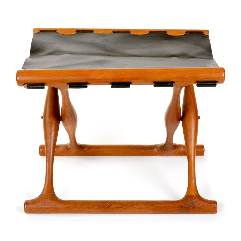 A teak folding stool with a black leather sling seat. Famed copy of oldest existing piece of furniture in Scandinavia.