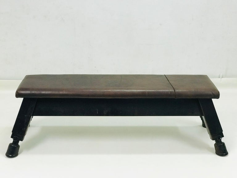This bench has the massive stable construction with strong leather with original patina. It has setting legs for different height. The dimension of the upper leather desk is 152 x 40 x 7 cm.