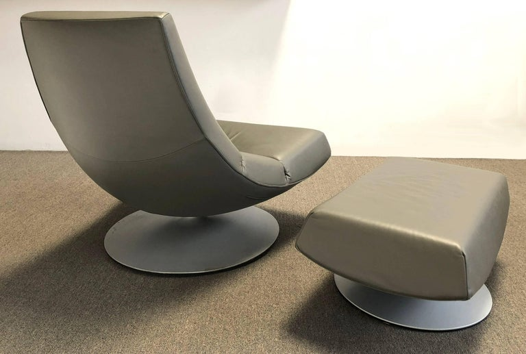 Leather lounge chair and ottoman designed by Geoffrey Harcourt for Artifort. Made in the Netherlands. Both chair and ottoman swivel on a powder coated aluminium base. This chair is used but is in fine condition. Designed for comfort and style. The