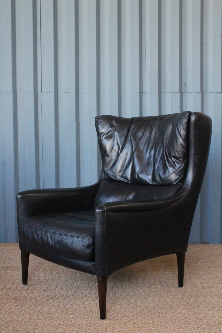 Leather lounge chair by Kurt Østervig, Denmark, 1950s. Original black leather is in fantastic condition. The legs have been replaced and copied as the originals in a stained oak. Overall wonderful condition with some age appropriate wear to the
