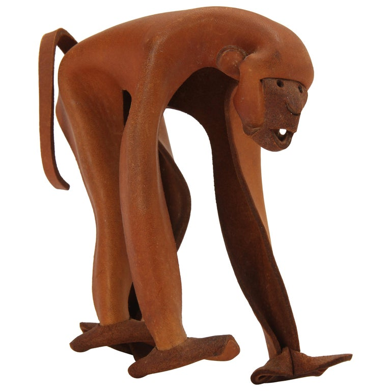 A monkey handcrafted from a pinched and riveted piece of leather.