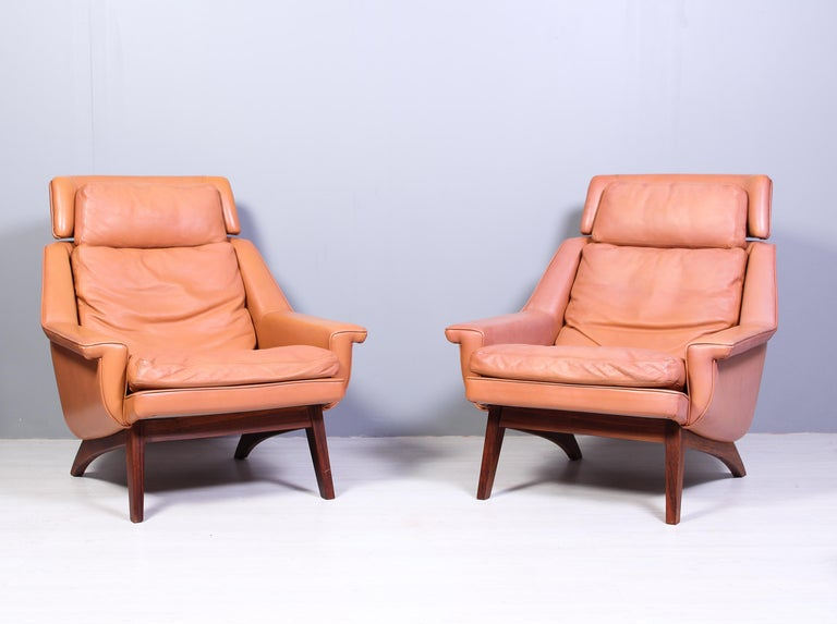 A pair of midcentury lounge chairs and an ottoman designed by Werner Langenfeld and produced by ESA in Denmark in the 1960s. The chairs and ottoman have a nice cognac colored leather upholstery and rosewood frames. This model with the rosewood frame