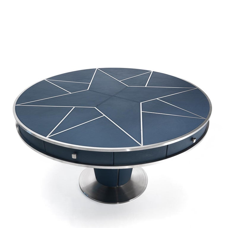 Effortlessly taking center stage in refined modern and contemporary decors, this round dining table flaunts an imposing silhouette whose frame is fashioned of steel and upholstered in blue-hued leather. The circular top is enlivened by luminous