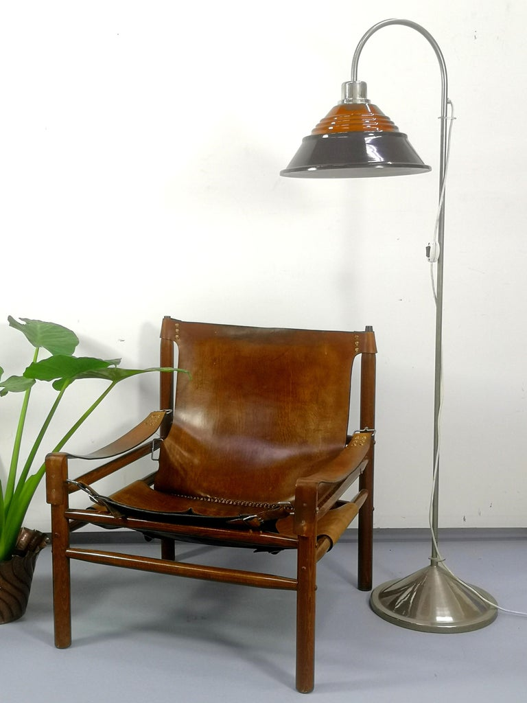 This sturdy raw leather and solid wooden armchair was made and designed in the 1970s.