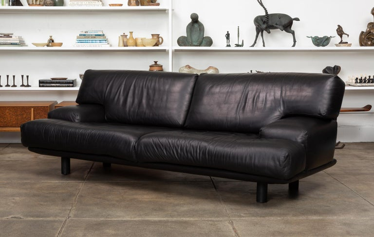 Black leather sofa by Brayton International, USA, circa 1980s. The sofa features a Minimalist low profile with wide sumptuous cushions and armrests, all upholstered in a soft black leather. The cushions sit atop an upholstered leather frame with