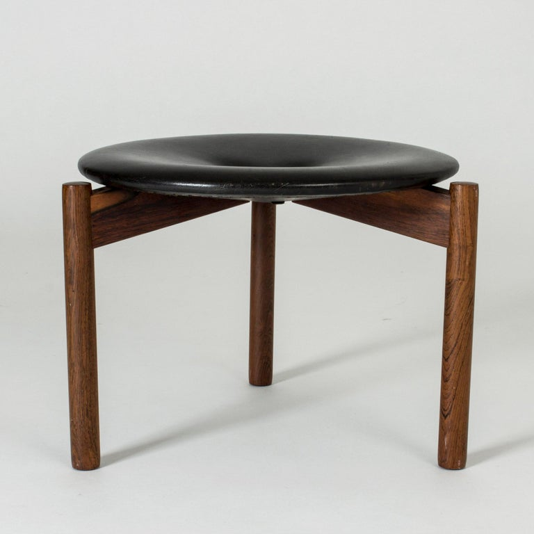Neat round stool by Uno & Östen Kristiansson, with a tripod rosewood base and black leather seat. Nicely patinated leather, three leather buttons in the middle.