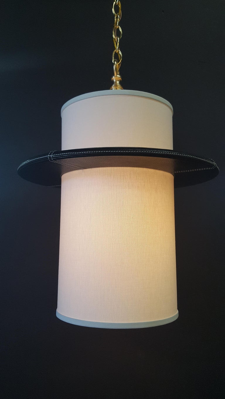 Top-stitched leather wrapped Adnet-inspired pendant by Paul Marra. With white linen shade, hand sewn top-stitched detailing, black leather, brass chain and canopy. The height of fixture to chain is 26