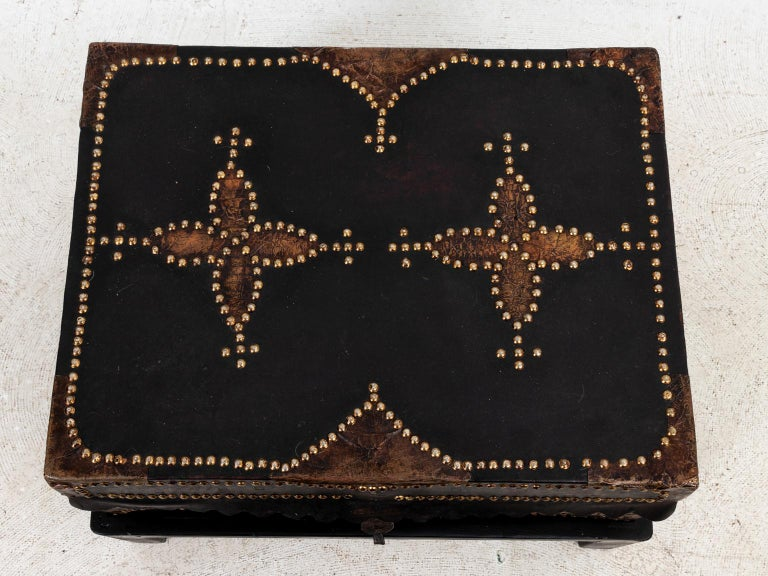 Black leather trunk on stand with brass tacks, circa 19th century. Made in Spain. Please note of wear consistent with age including distressed finish to the leather, patina to metal handles, and minor scratches on the bottom stand.