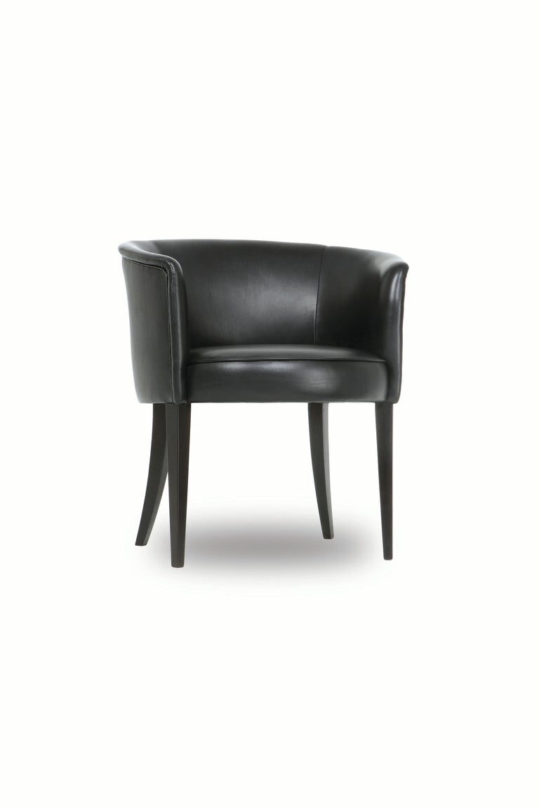 The Round chair has a tight upholstered seat and back. Seams are finished with self welts. Tapered front legs and curved back legs are made of blackened hardwood.   Made to order and handcrafted in the USA. Available in leather in a range of colors