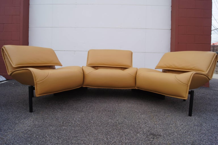 Designed by Vico Magistretti and produced by in 1984, the Veranda 3 sofa comprises three connected lounge chairs. The two at the end swivel on their fixed base to form a more intimate configuration. Each supple beige-colored leather seat has an