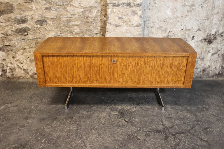Rare Mid-Century Modern Leif Jacobsen executive credenza, circa 1970. This high quality constructed credenza features beautiful exotic wood grain, tambour doors, a finished back, chrome cantilevered legs, and inset chrome banding on the top. Leif