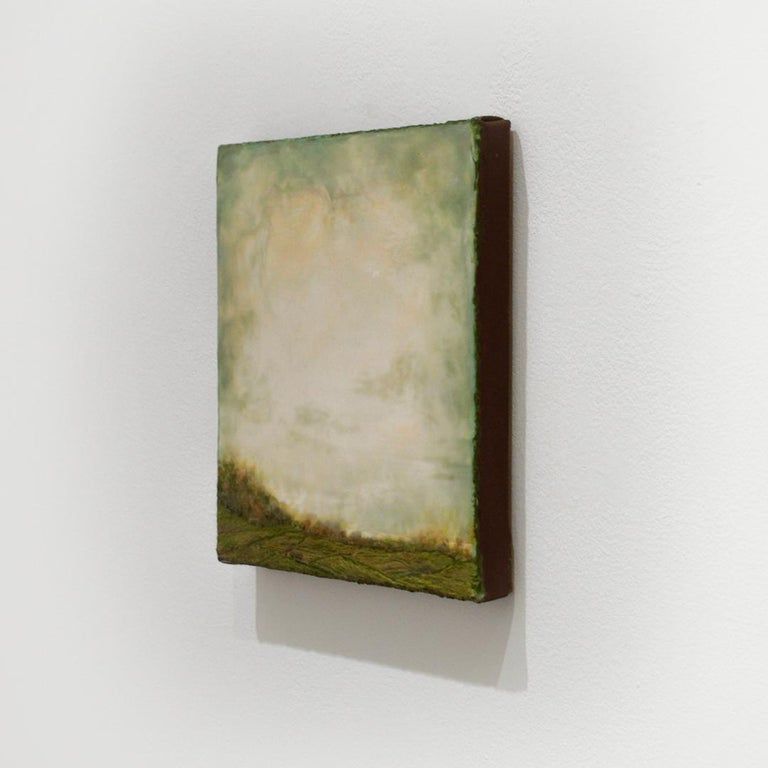 Hudson River School style encaustic landscape painting of a green country field with an expansive soft teal, light green and light yellow sky Untitled I, painted by Leigh Palmer in 2020  10 x 10 x 1 inch encaustic on linen mounted on panel  Signed,