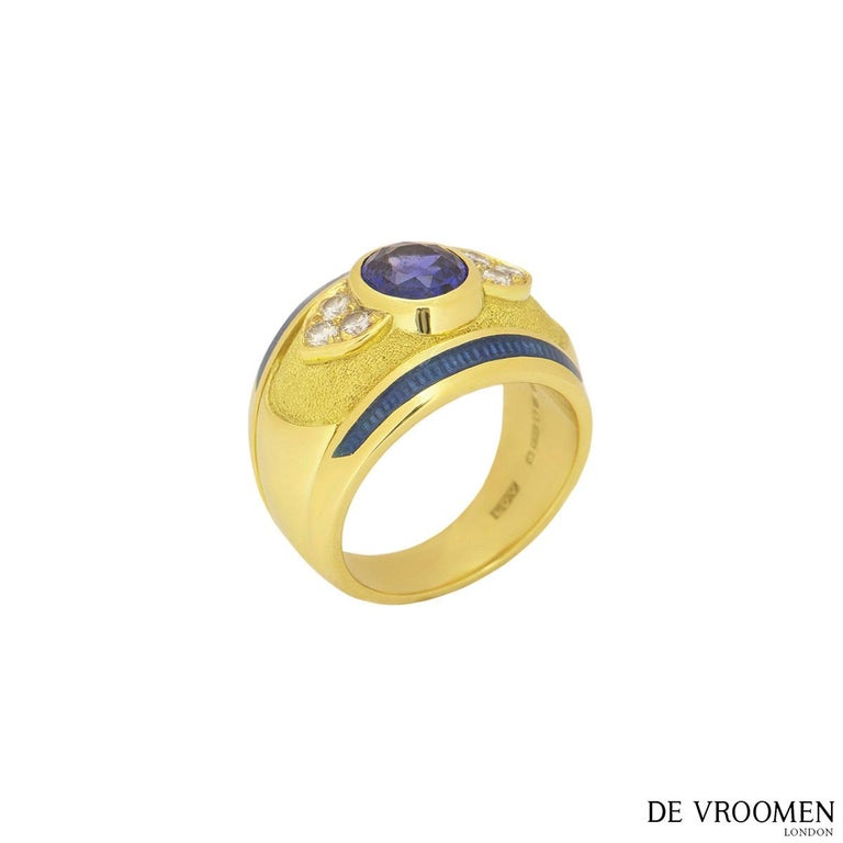 An 18k yellow gold diamond and sapphire ring by De Vroomen. The ring comprises of an oval shaped sapphire with an approximate weight of 1.40ct, 6 round brilliant cut diamonds with a total weight of 0.24ct and blue enamel detailing. The ring is