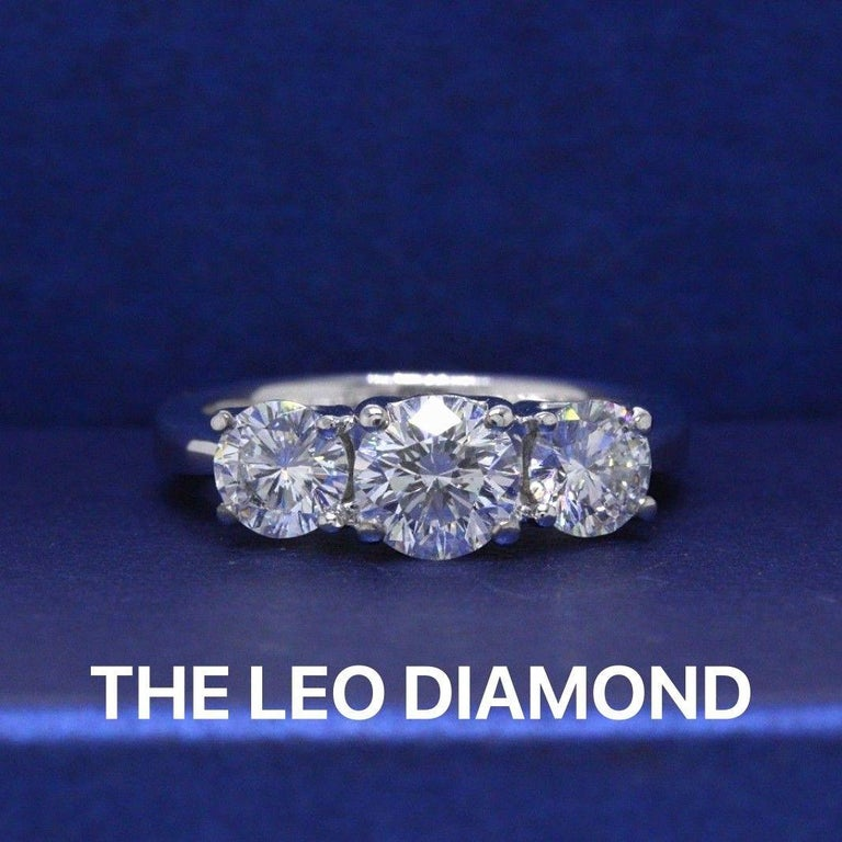 THE LEO DIAMOND  Style:  Three - Stone Design Serial Number:  LEO 187861 Certificate:  IGI # 3149349U Metal: 14KT White Gold Size:  4.5 - Sizable  Total Carat Weight:  1.51 TCW Diamond Shape:  Leo Round Description:  Center:  0.71 CTS F-G Color
